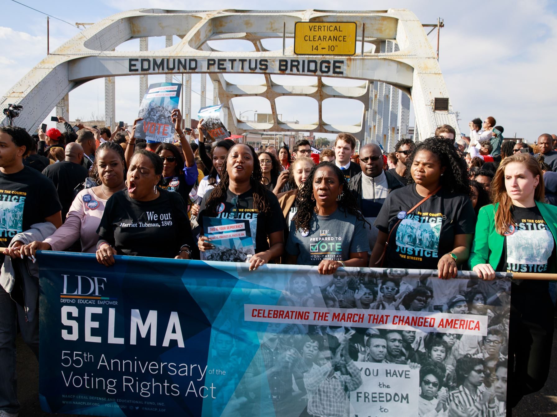 Marchers on Edmund Pettus bridge, commemorating the 55th Anniversary of the Voting Rights Act with a banner
