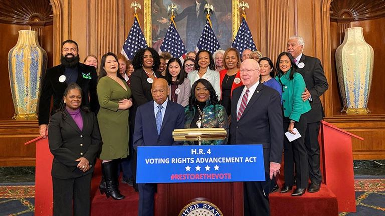 People in suits behind sign with text 'Voting Rights Advancement Act'