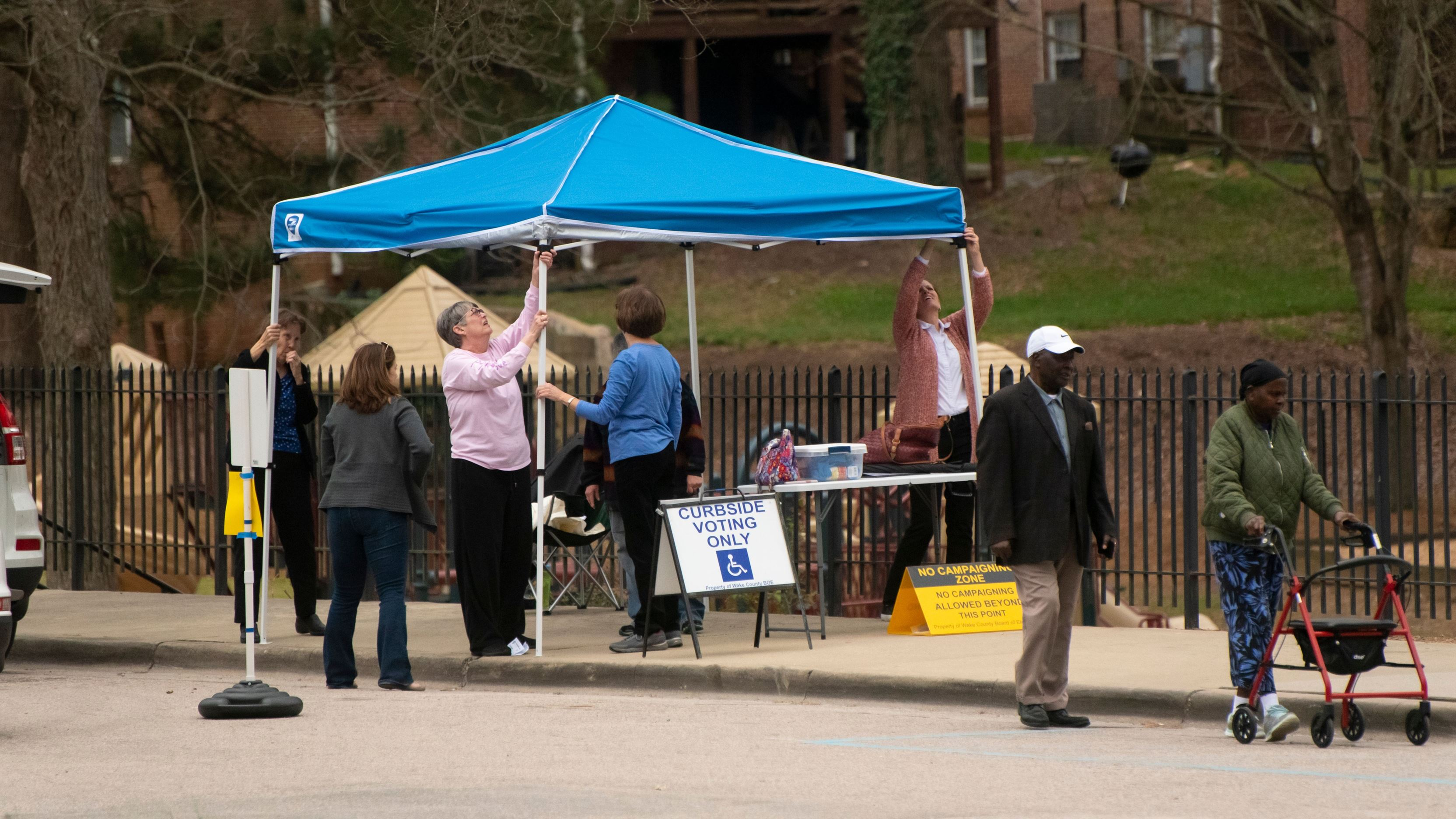 People assembling a curbside voting location