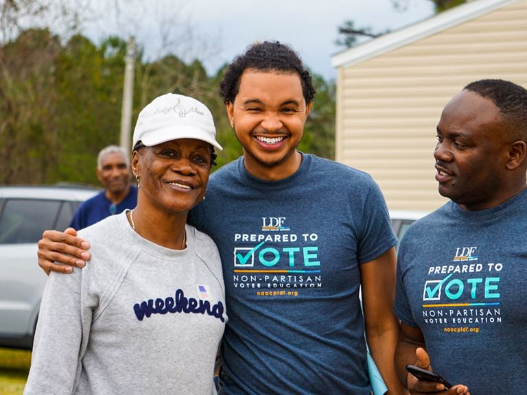 Picture of three Black people smiling with voting shirts.